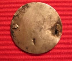 Silver ornamental disc pin backside